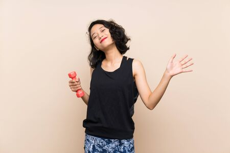 Young Asian girl making weightlifting over isolated background saluting with hand with happy expression Reklamní fotografie