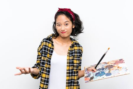 Young artist woman holding a palette over isolated white background making doubts gesture while lifting the shoulders