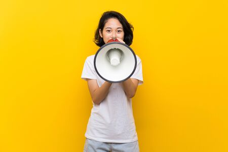 Asian young woman over isolated yellow wall shouting through a megaphone 版權商用圖片