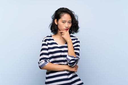 Asian young woman over isolated blue background thinking