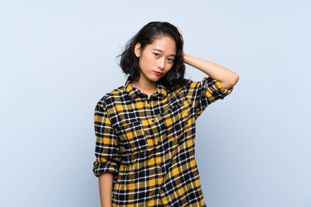 Asian young woman over isolated blue background with an expression of frustration and not understanding Imagens
