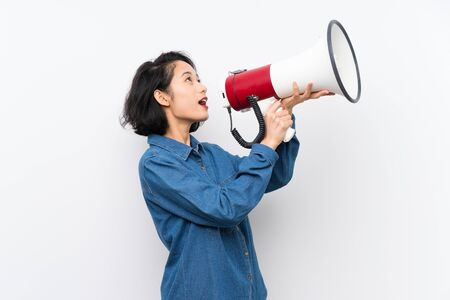 Asian young woman over isolated white background shouting through a megaphone Stockfoto
