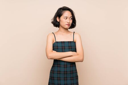 Asian young woman over isolated yellow wall with confuse face expression