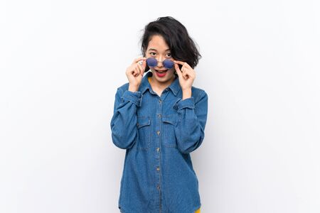 Asian young woman over isolated white background with glasses and surprised