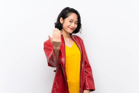 Asian young woman over isolated white background inviting to come with hand. Happy that you came