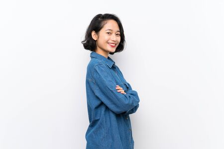 Asian young woman over isolated white background with arms crossed and looking forward