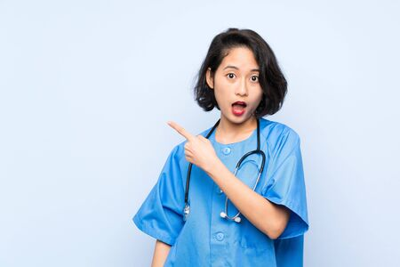 Surgeon doctor woman surprised and pointing side Stok Fotoğraf
