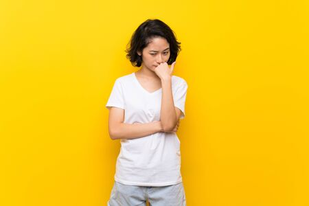 Asian young woman over isolated yellow wall having doubts