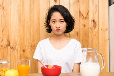 Asian young woman having breakfast milk sad