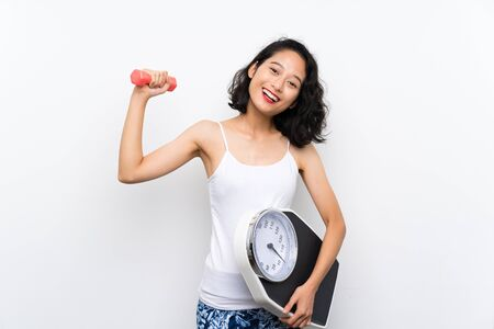 Young Asian girl making weightlifting and with weighing machine