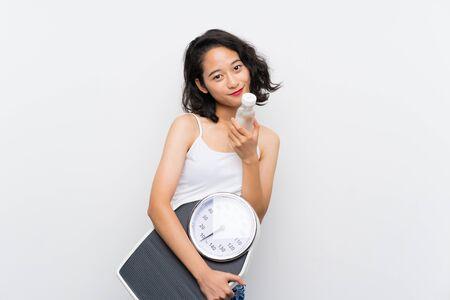 Jeune fille asiatique avec une machine de pesage sur fond blanc isolé Banque d'images