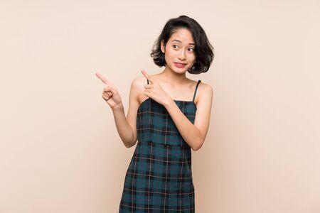 Asiatische junge Frau über isolierter gelber Wand erschrocken und zeigt auf die Seite