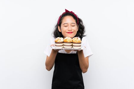 Young asian girl holding lots of muffin cake over isolated white background