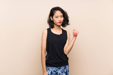 Young Asian girl making weightlifting over isolated background with sad expression Reklamní fotografie
