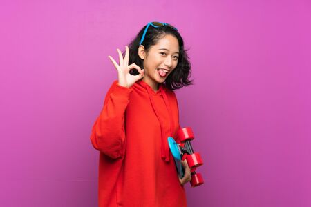 Asian young girl with skate over purple background