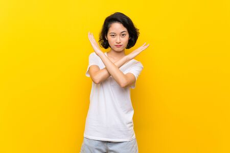 Asian young woman over isolated yellow wall making NO gesture