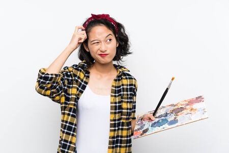 Young artist woman holding a palette over isolated white background having doubts and with confuse face expression Stock Photo