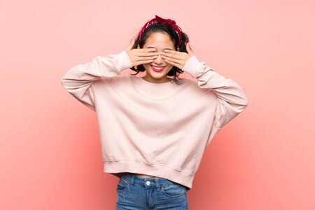 Asian young woman over isolated pink background covering eyes by hands