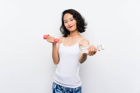 Young Asian girl making weightlifting and with a bottle of water