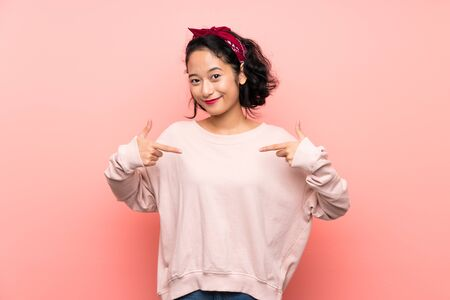 Asian young woman over isolated pink background proud and self-satisfied Foto de archivo