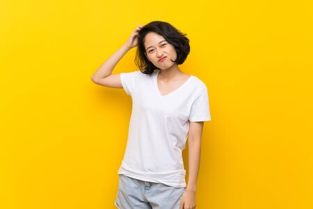 Asian young woman over isolated yellow wall having doubts while scratching head 免版税图像