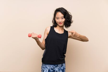 Young Asian girl making weightlifting over isolated background and pointing it