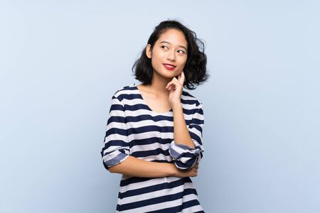 Asian young woman over isolated blue background thinking an idea while looking up Reklamní fotografie