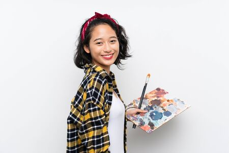 Young artist woman holding a palette over isolated white background smiling a lot