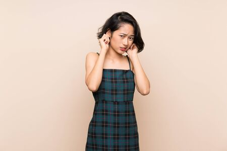 Asian young woman over isolated yellow wall frustrated and covering ears Stock Photo