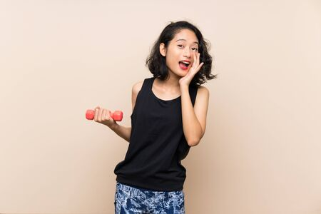 Young Asian girl making weightlifting over isolated background shouting with mouth wide open