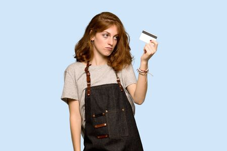 Young redhead woman with apron taking a credit card without money over blue background