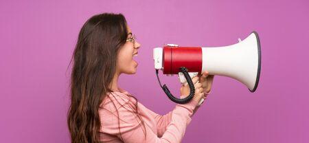 Teenager girl over purple wall shouting through a megaphone Stockfoto