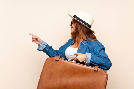 Redhead traveler girl with suitcase over isolated background pointing to the side to present a product
