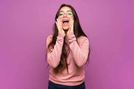 Teenager girl over purple wall shouting and announcing something
