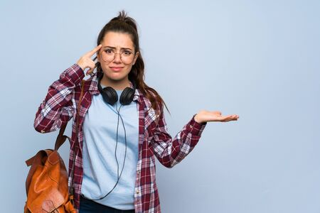 Teenager student girl over isolated blue wall making the gesture of madness putting finger on the head