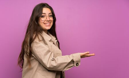 Teenager girl over purple wall extending hands to the side for inviting to come