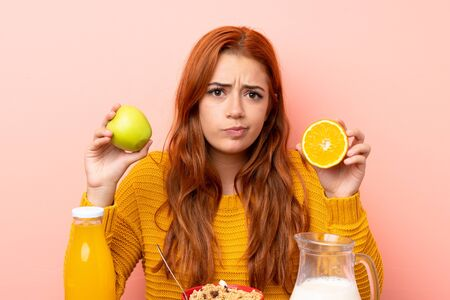Teenager redhead girl having breakfast in a table and having doubts