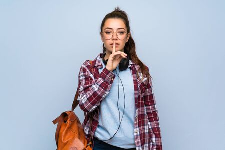 Teenager student girl over isolated blue wall showing a sign of silence gesture putting finger in mouth