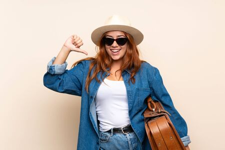 Redhead traveler girl with suitcase over isolated background proud and self-satisfied