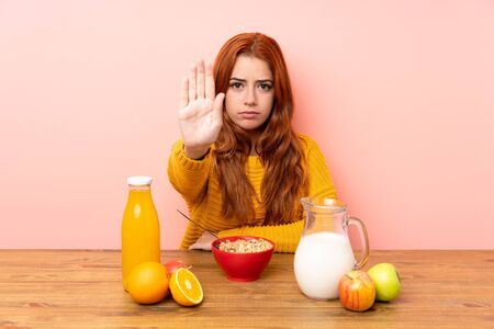 Teenager redhead girl having breakfast in a table making stop gesture with her hand Stok Fotoğraf