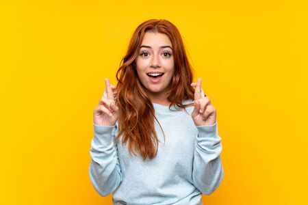 Teenager redhead girl over isolated yellow background with fingers crossing and wishing the best