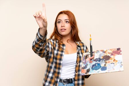 Teenager redhead girl holding a palette over isolated background touching on transparent screen