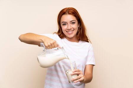 Teenager redhead girl holding a glass of milk over isolated background Stok Fotoğraf
