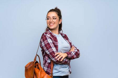 Teenager student girl over isolated blue wall with arms crossed and happy