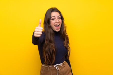 Teenager girl over isolated yellow wall with thumbs up because something good has happened