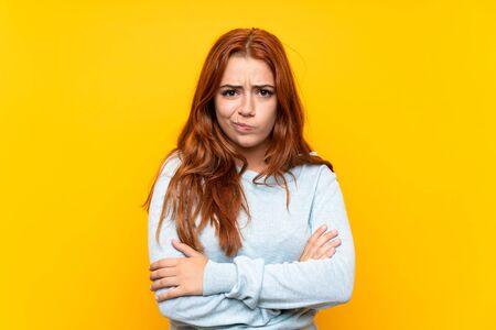 Teenager redhead girl over isolated yellow background feeling upset