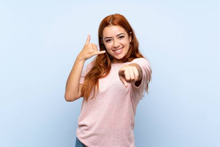 Teenager redhead girl over isolated blue background making phone gesture and pointing front Stok Fotoğraf