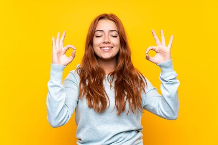 Teenager redhead girl over isolated yellow background in zen pose Фото со стока