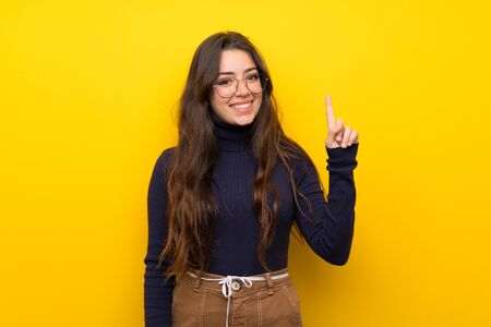Teenager girl over isolated yellow wall showing and lifting a finger in sign of the best Stok Fotoğraf