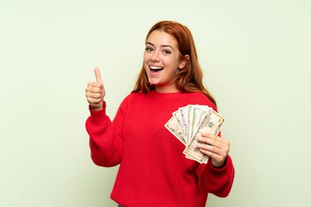 Teenager redhead girl with sweater over isolated green background taking a lot of money Stockfoto